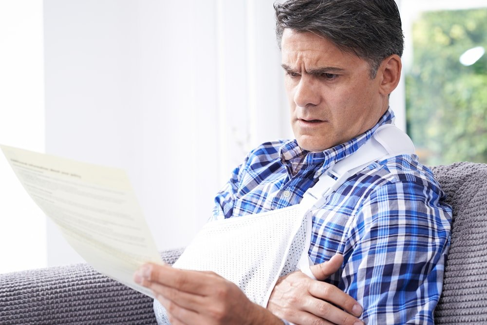 Man reading compensation claim from moped accident.